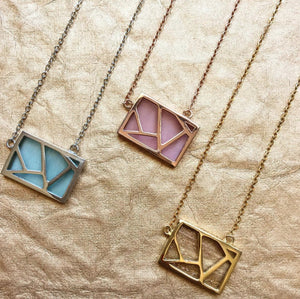 blue, pink and gold Necklace - Lattice Necklace on a beige background on a tilt