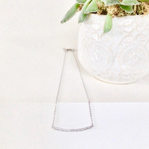 Little Jewels - Curved Necklace With Crystals sitting on edge of table with a plant