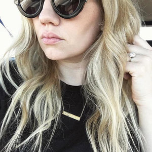 Blond woman wearing black sunglasses and shirt wearing gold Mantra Engraved Horizontal Necklace