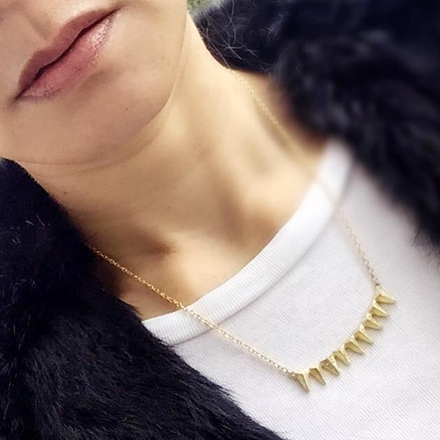 Woman wearing white shirt and black fur wearing Mantra Multi Triangle Necklace