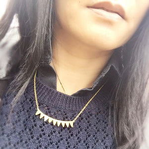 woman in navy sweater and black shirt wearing Mantra Multi Triangle Necklace
