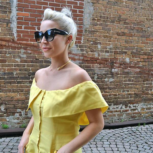 Taylor Stone of Stone Files wearing bright yellow off shoulder dress with Mantra Small Dagger Collar