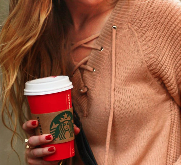 Blogger Upbeat Soles holding a cup of Starbucks coffee wearing Cube Ring