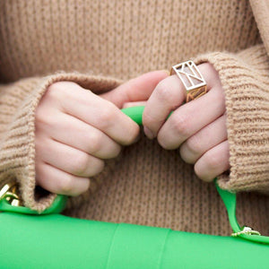 Blogger Veronica of Bittersweet Colours Ring wearing beige sweater holding green bag with Lattice Square Cocktail Ring