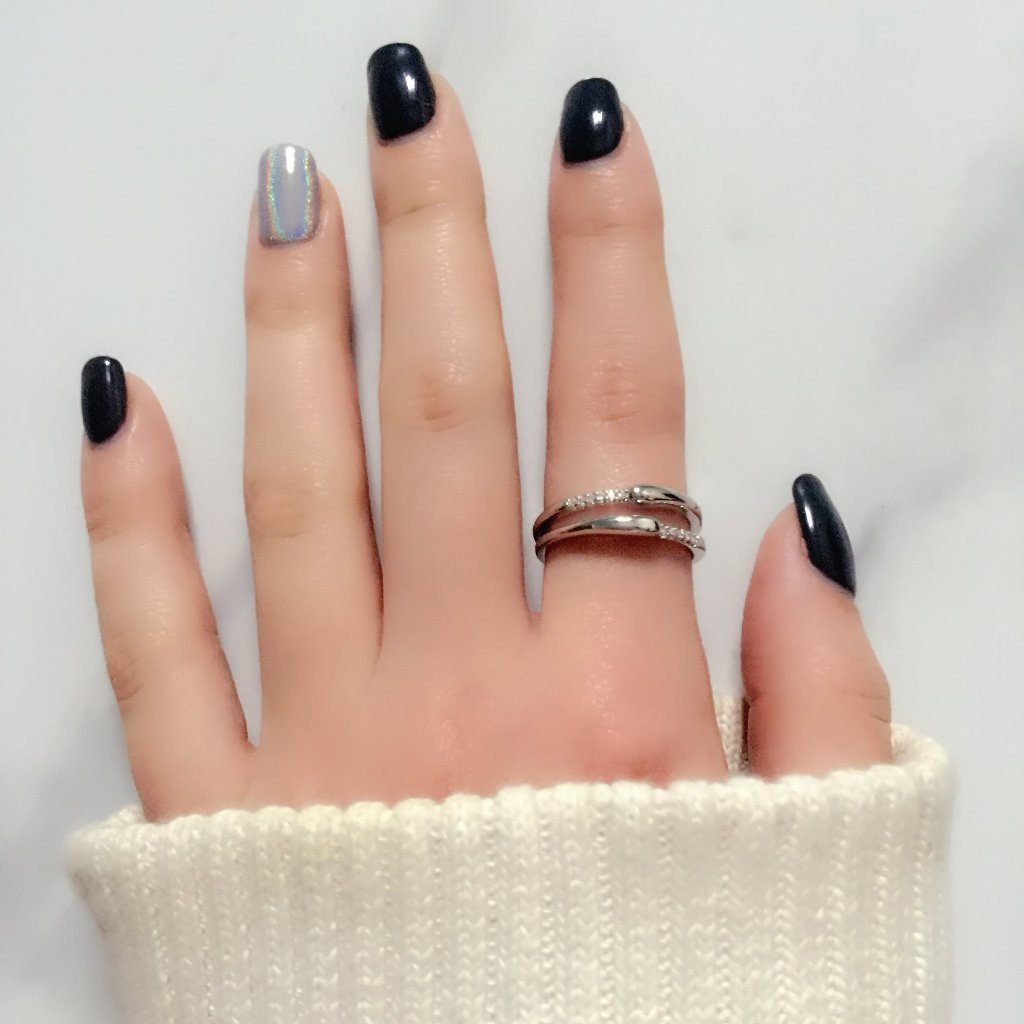 black and grey manicure hand opened flat on table with sweater cuff wearing Little Jewels - Double Tiered Ring With Crystals