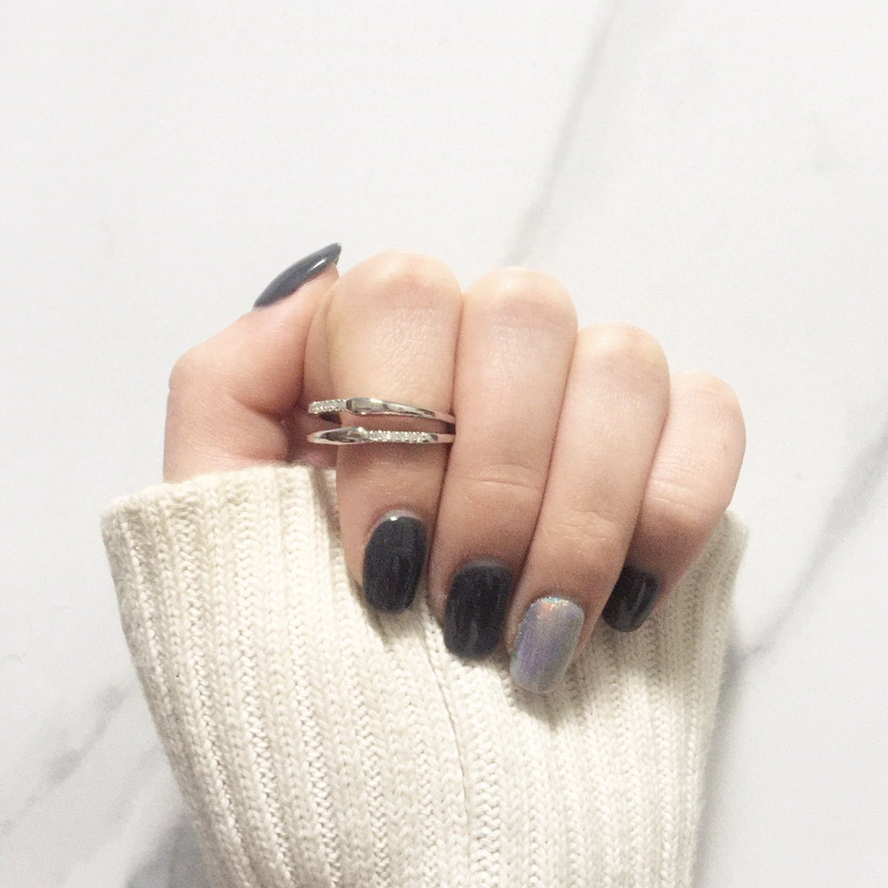 black and grey manicure hand closed flat on table with sweater cuff wearing Little Jewels - Double Tiered Ring With Crystals