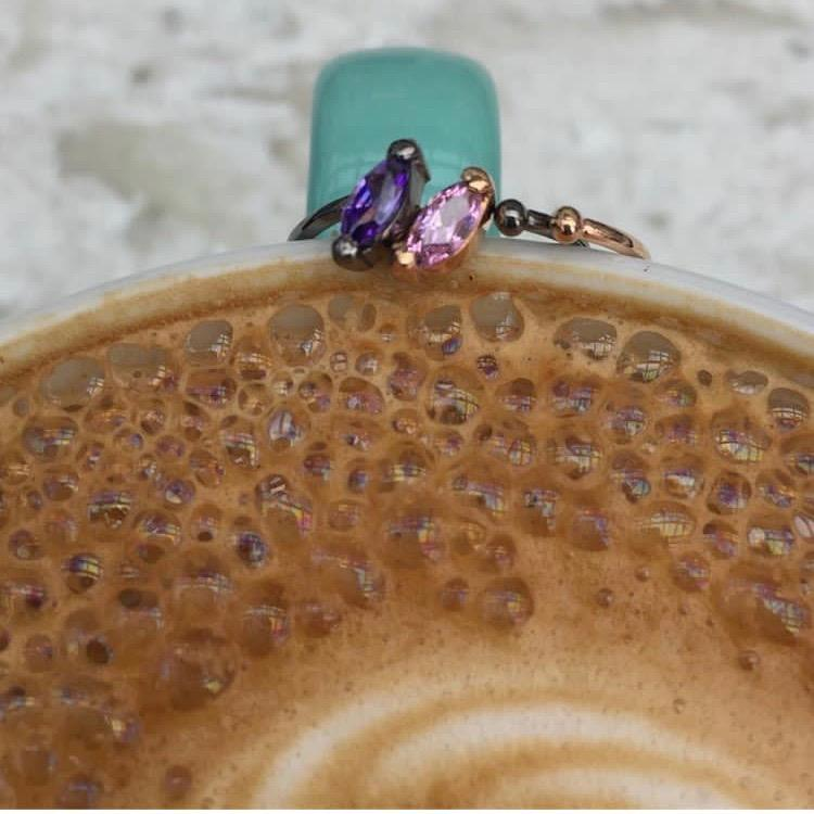Two Little Jewels - Marquise Cut Open Ring With Swarovski Crystals sitting on a rim of a latte