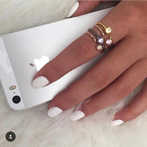 woman with white manicure holding silver iPhone wearing 4 Little Jewels - Round Cut Open Ring With Swarovski Crystals stacked