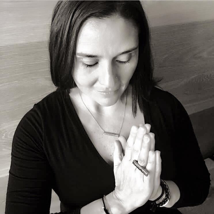 Black and White image of Khadija Muhaisen of Khadija's Adventures of the Soul in prayer position wearing Mantra Long Knuckle Ring With Edge