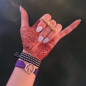 Hang Loose sign with henna and elastic bracelets wearing Mantra Long Knuckle Ring With Edge