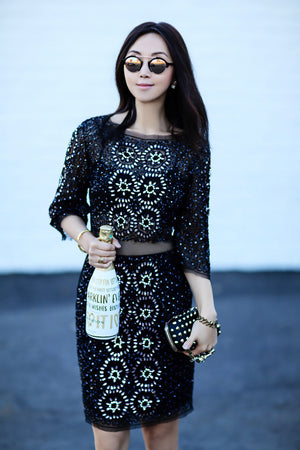 Jane fitfabfun mom blogger in black dress holding a bottle of champagne wearing Lattice Open Unisex Ring with White Sapphires, gold