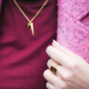 Veronica of Bittersweet Colours in dark pink jacket and sweater wearing Mantra Rectangular Ring off Shank with Beading in Tiger's eye and Mantra Dagger Necklace with Natural Stone Necklace