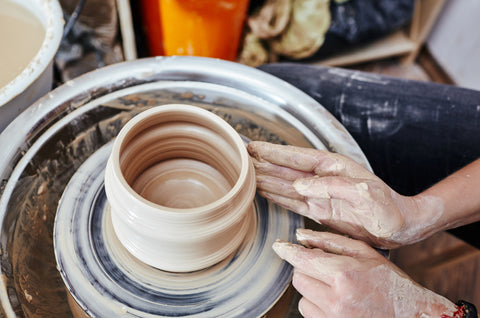 A person throws a clay vessel on a pottery wheel