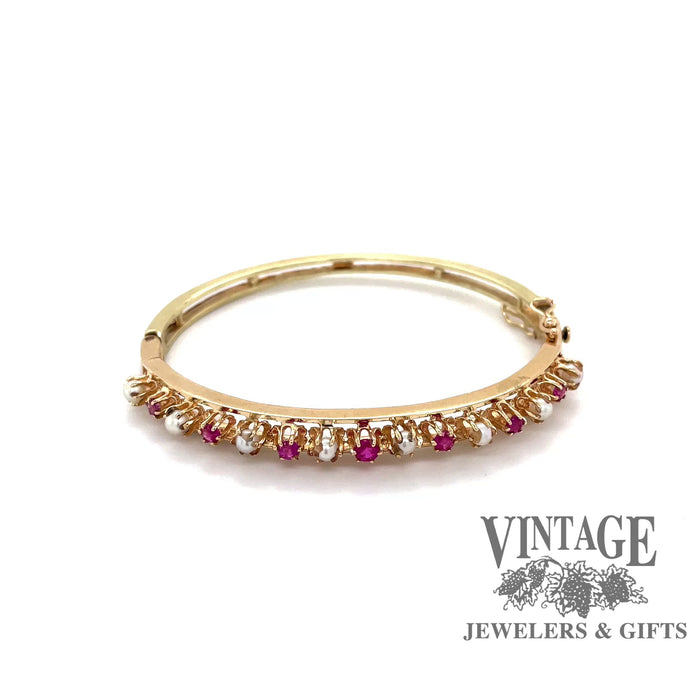 Revolving video of 14 karat yellow gold ruby and pearl bangle bracelet