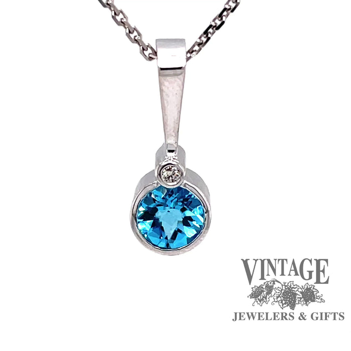 Revolving video of 14 karat white gold blue topaz pendant with diamond accent
