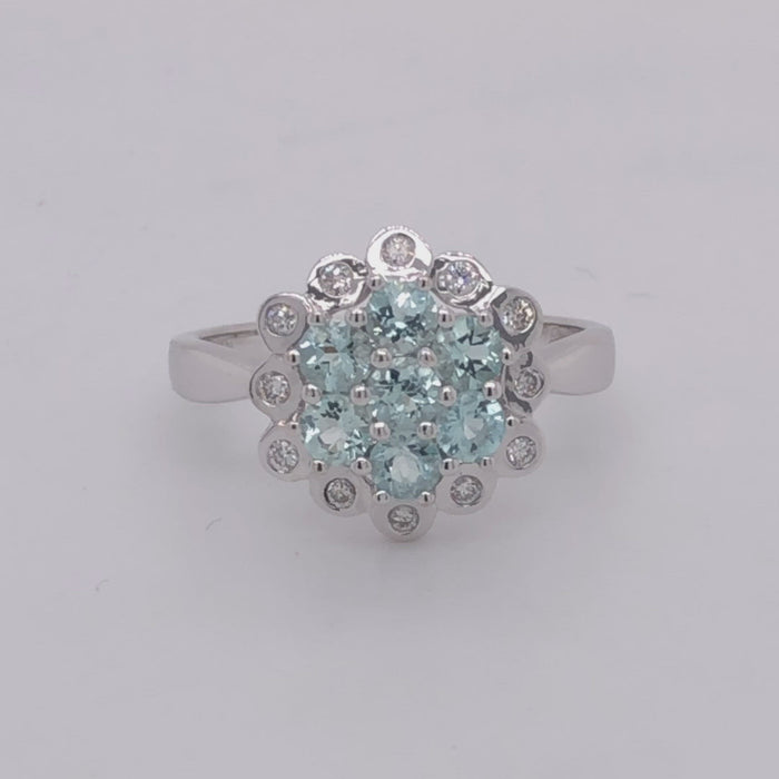 18 karat white gold aquamarine cluster ring with diamond halo.