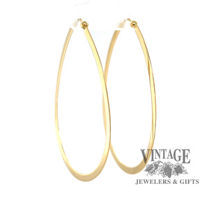 Large flat 14K gold teardrop shaped hoops from angle