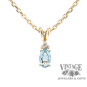 14 karat yellow gold pendant with natural oval shaped aquamarine and diamond accents