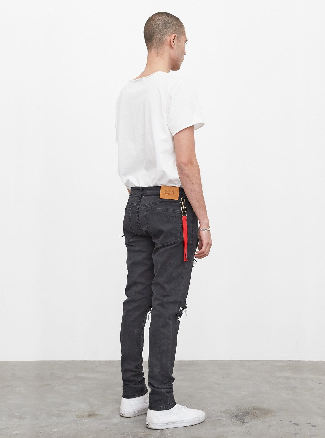 Washed faded black destroyed distressed denim jeans by profound aesthetic