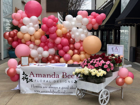 Table with big baloon display and flower cart holding red, pink, and white flowers.