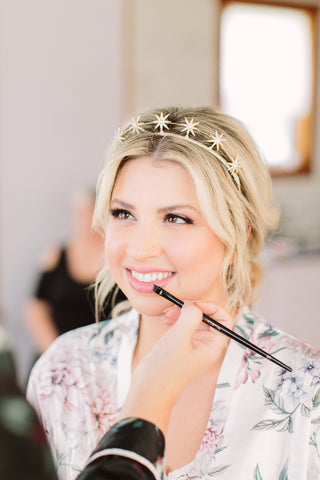 Close up of bride wearing boho crown with makeup artist.
