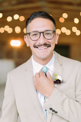 Groom in glasses wearing a bolo tie and modern boutonniere.
