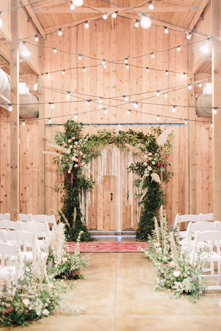 Houston Texas wedding natural wood with string lights and white chairs surrounded by flowers.