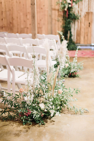 Close up of white chairs and wedding ceremony flower arrangements