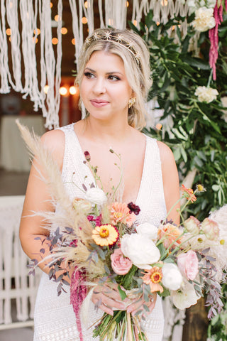 Close up of young bride with asymmetrical rustic wedding flowers.