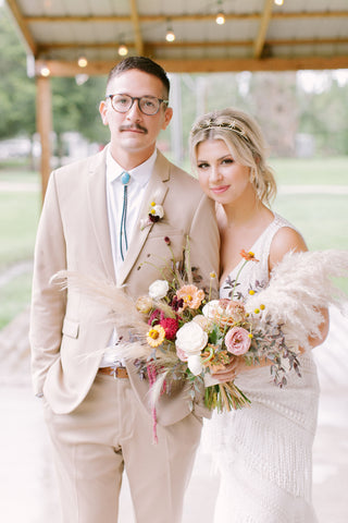 Young bride holding boho asymmetrical bouquet and groom with bolo tie.