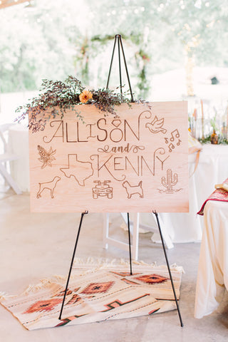 Laser cut wooden sign with bride and groom name, Texas symbols, and dogs accented by flowers.