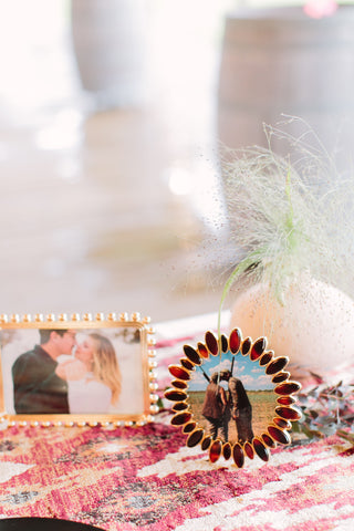 Close up of bride and groom table with textured boho flowers and framed photos of the couple.