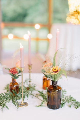 Boho wedding table decor with tapered camdles and brown medicine bottles for vase.