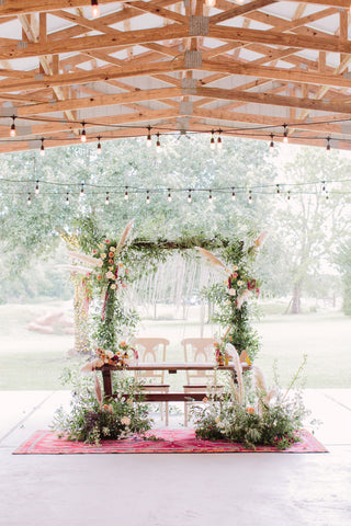 Head table at outdoor barn wedding with flower alter by Houston florist and string lights.