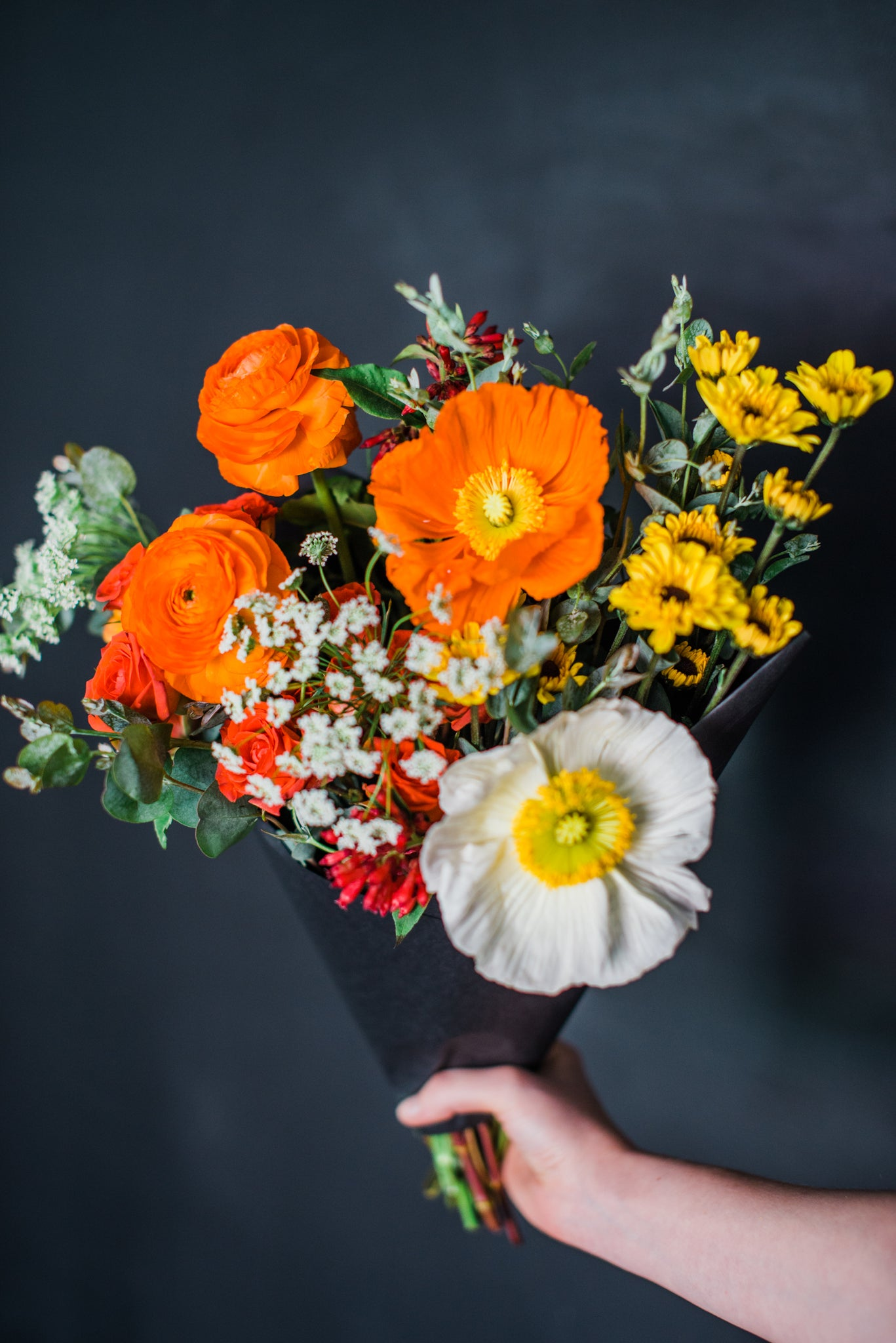 Hand holding a bouquet of colorful flowers against a dark background.