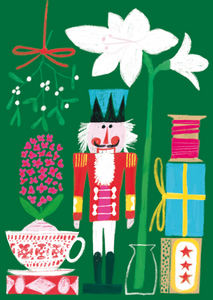 Green background with colorful nutcracker front and center between a white amaryllis and a pink hyacinth in teacup. Mistletoe hangs in the upper left corner and a stack of gifts and pink thread on a wooden bobbin sit in the lower right corner.