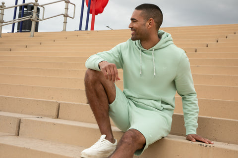 man wearing a threadbare hoodie and shorts sitting down