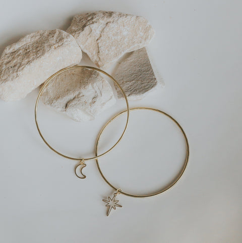 Flatlay of moonlight bangle bracelets in brass with star and moon