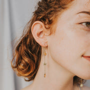 Model wearing dangle star earrings in gold