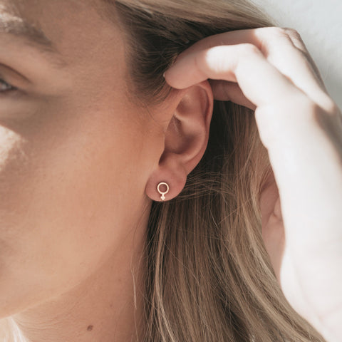 Model wearing Brass Virtue Studs featuring the International Woman Sign.