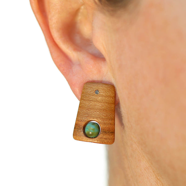 Small peach wood post earrings with painted green Czech beads on model.