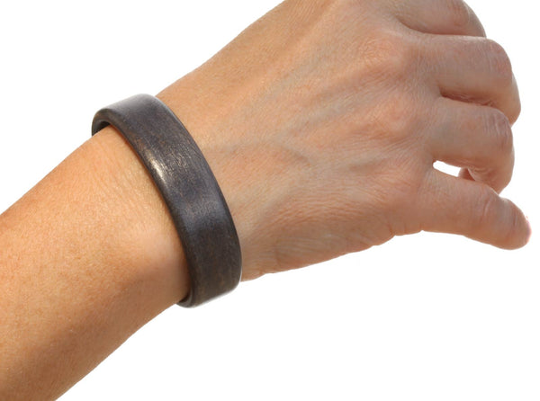 Steam bent grey sycamore wood cuff bracelet on model.