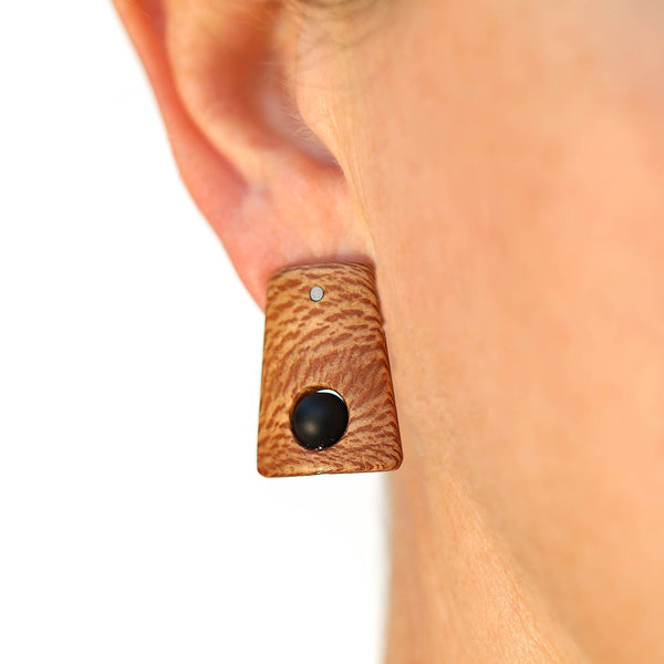 Small sycamore wood post earrings with onyx beads on model.