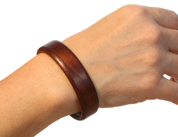Steam bent walnut wood cuff bracelet on model.