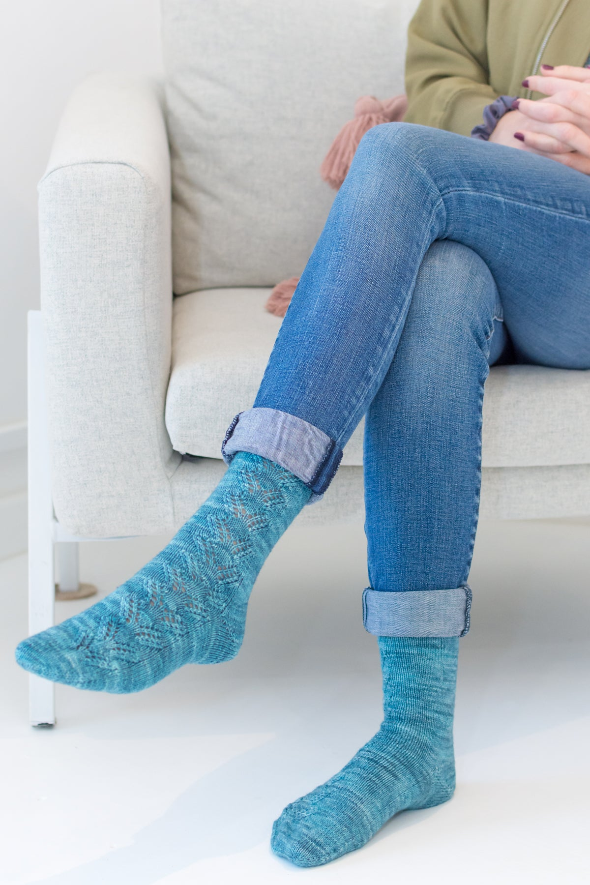 Woman sitting in chair modelling handknit socks with lace
