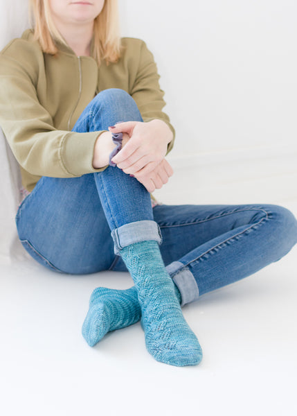 Woman sitting up against a wall modelling hand knit socks