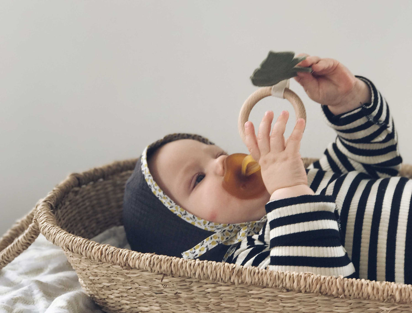 baby lying in a moses basket clutching a wooden teether