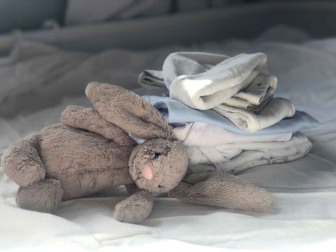 soft toy bunny in front of a pile of clothes on a bed.