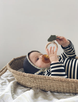 Baby laying in a basket playing with a teething toy