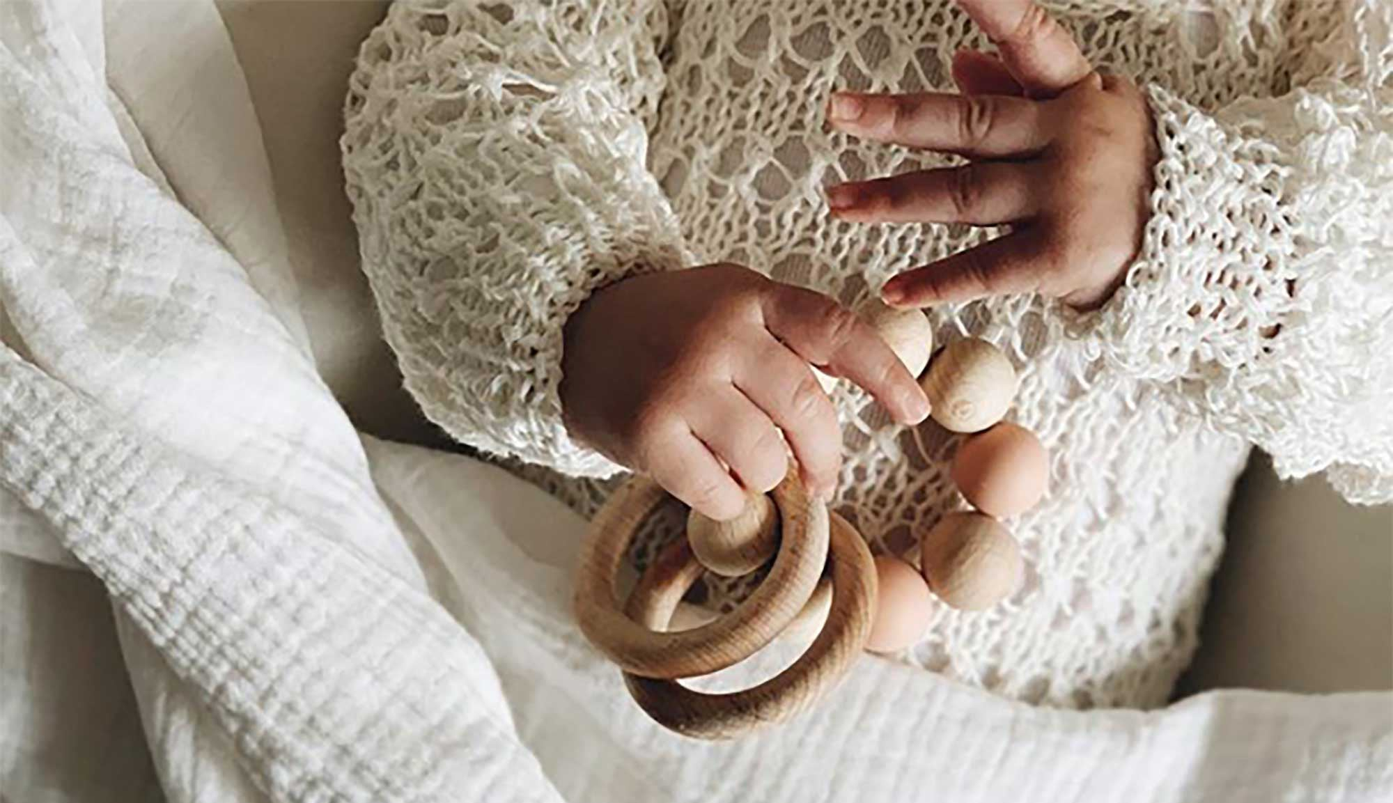 Baby clutching a wooden teether
